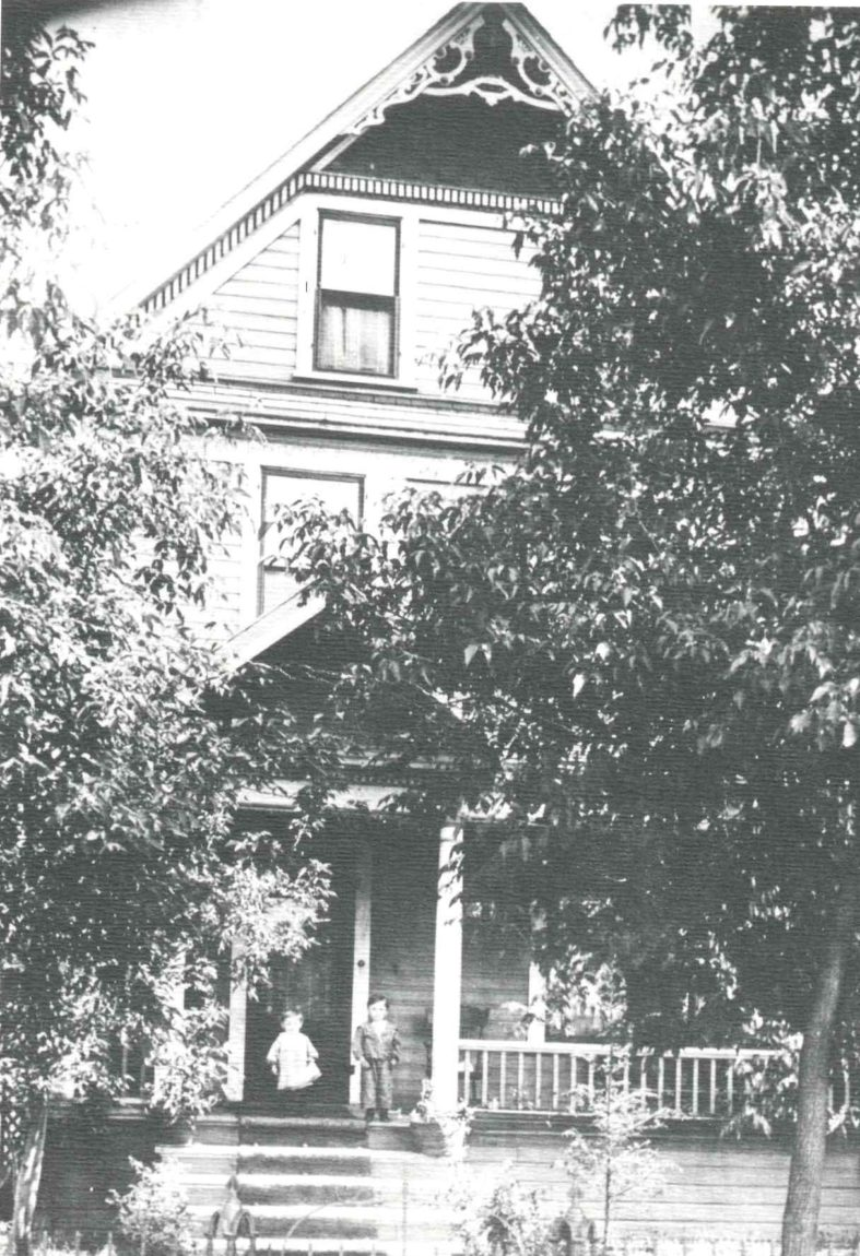 A grainy black and white photo shows a house partially obstructed by trees. Two children stand on the front porch.