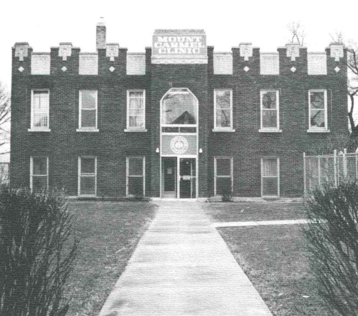 A grainy black and white photo shows a brick building that says Mount Carmel Clinic on it.