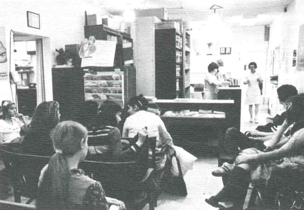 A grainy black and white photo shows the waiting room of the clinic filled with patients. Three medical staff are working in the background.