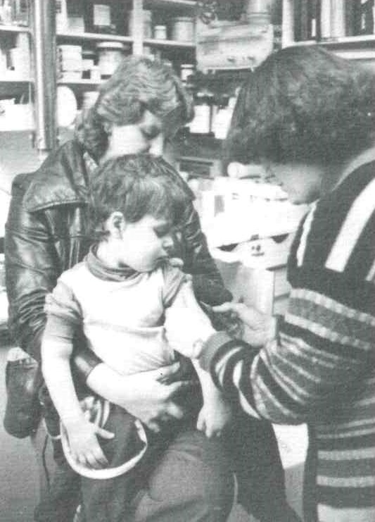 A grainy black and white photo shows a parent holding young child as they receive a vaccination in their arm from medical staff.
