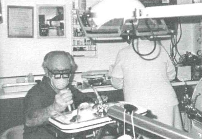 A grainy black and white photo shows two medical staff in the clinic during the 1970s. One wears a mask with thick glasses on and is operating a piece of medical equipment. The other has their back to the camera and is working at a counter.