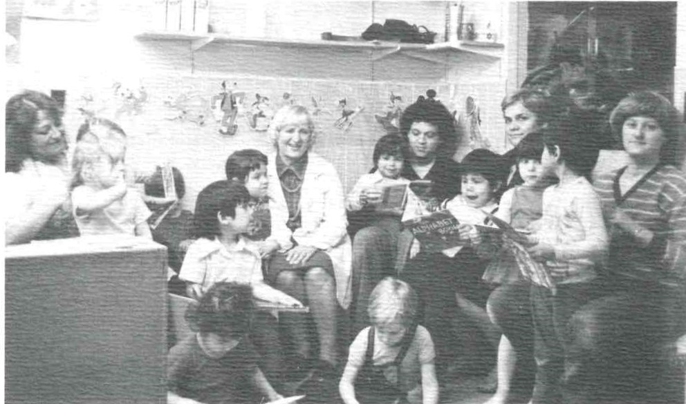 A grainy, black and white photo from the 1970s of Anne Ross wearing a white lab coat and sitting with children from the daycare.