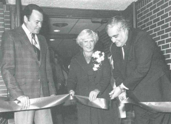 A grainy black and white photo shows Anne Ross standing alongside two politicians, holding a large ribbon outside the doors of Anne Ross Day Nursery. One of the politicians is cutting the ribbon with a pair of scissors.