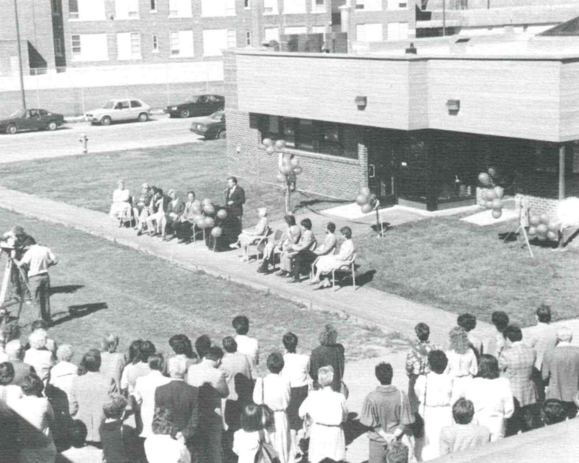 A grainy black and white photo from the 1980s shows lots of people attending a grand opening event for the Anne Ross Day Nursery. There are several large bundles of balloons and a podium with someone speaking to the crowd.