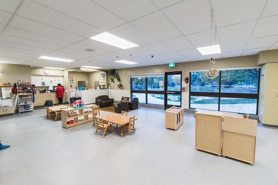 Interior of the Anne Ross Day Nursery. A brightly lit room with tiny, children's furniture, and a wall of windows looking out at the backyard play area.