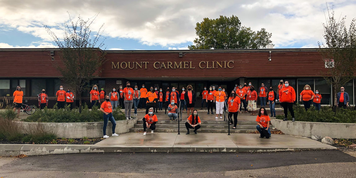 Mount Carmel Clinic team posing in front of building during pandemic, all staff members are wearing masks