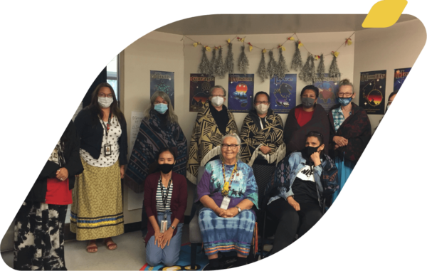 Participants, staff and Elders standing together for a photo. Many are dressed in Indigenous ribbon skirts. Drying sage bundles hang in the background