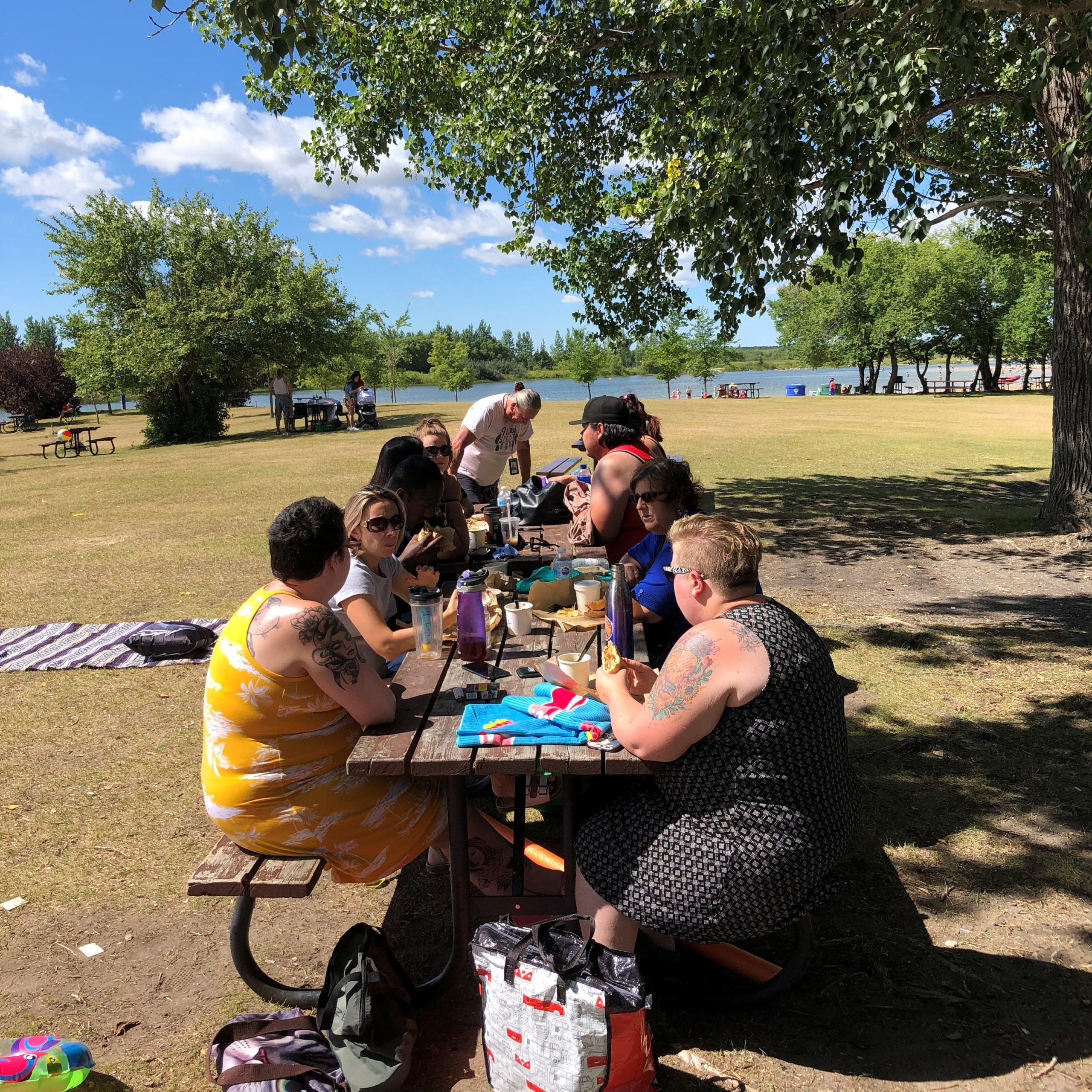 A group of co-workers sitting at a picnic table in front of a beach.